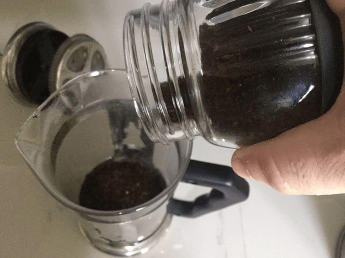 Adding ground coffee to French Press