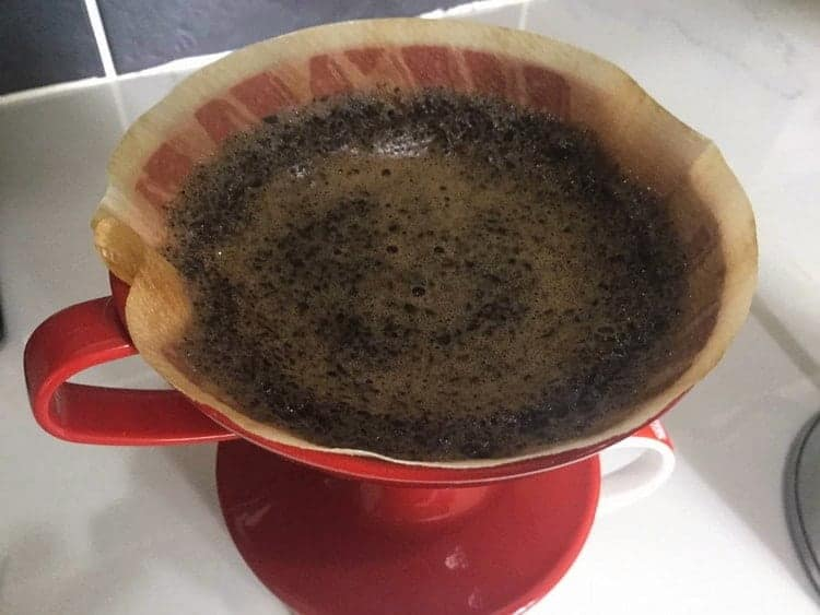 Hot water added to coffee grounds