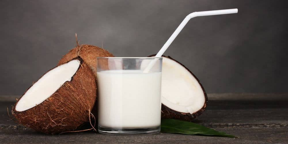 Halved Coconut and glass of milk