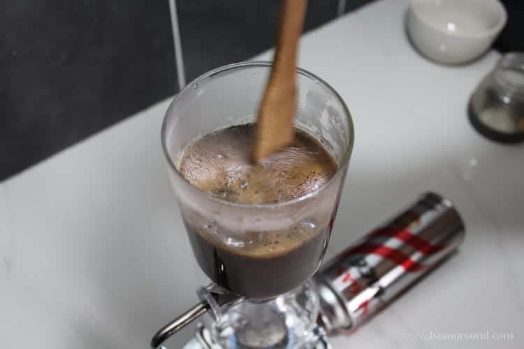 stirring the coffee with a wooden spoon