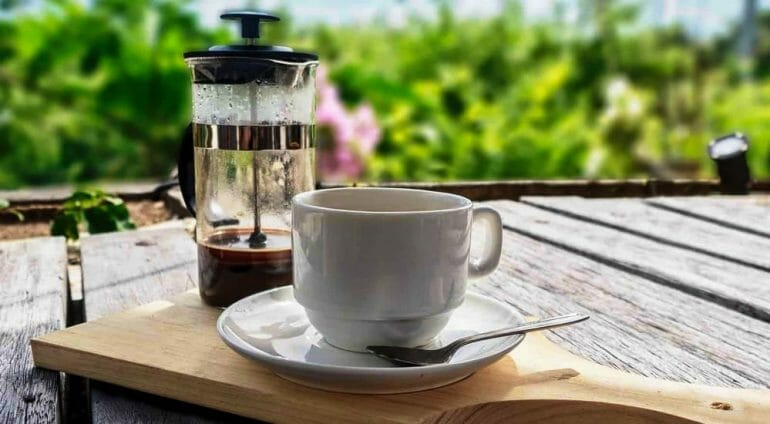 French press coffee on a wooden table outside